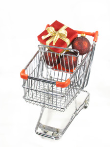 A christmas package with ornaments in a miniature shopping cart.
